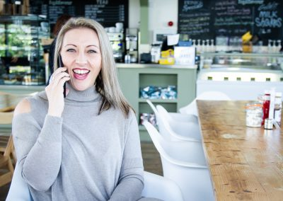 lady laughing on phone in a coffee shop